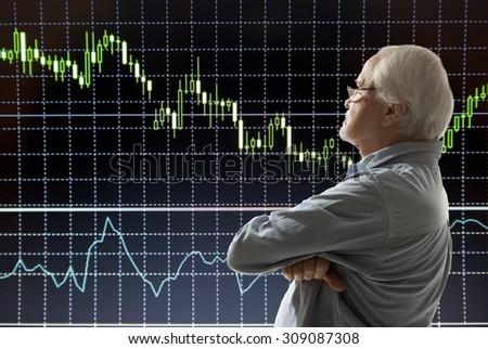 Aged stock trader looking at monitors - stock photo