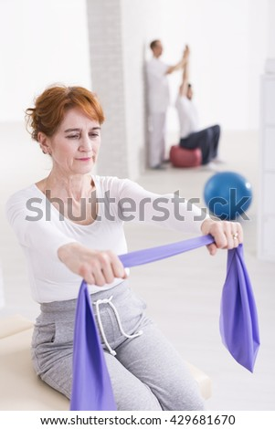 Aged strong woman trying to exercise her arms with elastic band during rehabilitation in physiotherapist's office