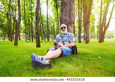 Aged stylish man is sitting under the tree on green grass and listening to music on his smart phone