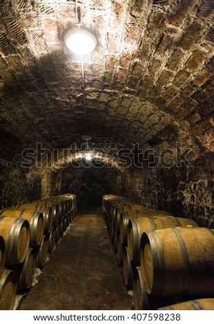 Aged traditional wooden vine barrels lined up in cool and dark vine cellar - stock photo