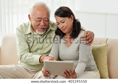 Aged Vietnamese man showing his wife how to use tablet computer - stock photo