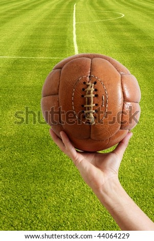 Aged vintage retro football leather ball in man hand grass field [Photo Illustration]