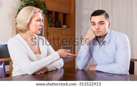 Aged woman and young boyfriend discussing something with serious faces at home