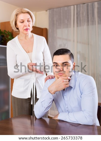 Aged woman and young boyfriend discussing something with serious faces. Focus on guy - stock photo