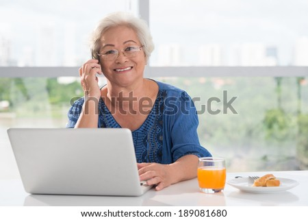 Aged woman calling on the phone while working on her computer - stock photo