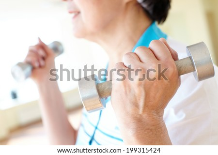 Aged woman doing physical exercise with barbells - stock photo