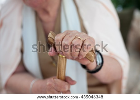 Aged woman hands holding wooden walking stick - stock photo