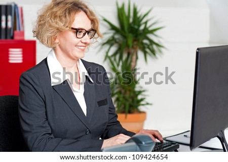 Aged woman in office wearing eyeglasses working on computer - stock photo