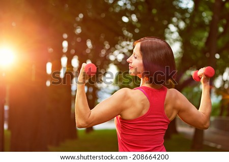 Aged woman working out with small dumbbells in the park in the morning. - stock photo