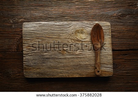 Aged wood cutting board copyspace background with olive tree wood spoon