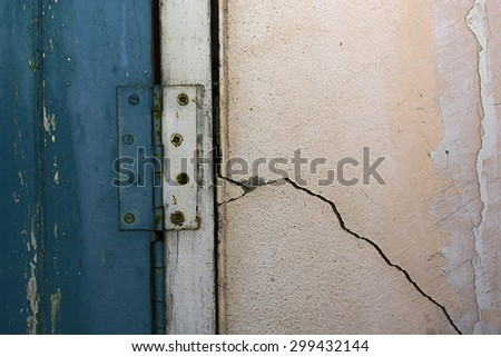 Aged wooden window with rusty hinges and shows structural damage wall crack - stock photo
