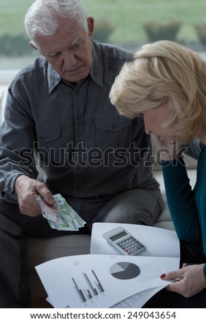 Aged worried marriage looking at home budget - stock photo