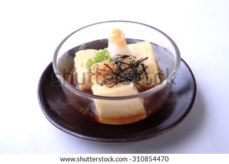 Agedashi tofu isolated on white background, hot tofu dusted with potato starch and deep fried. - stock photo
