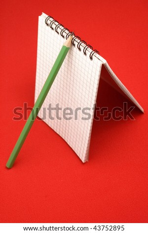 Agenda and pencil on red backgrounds - stock photo