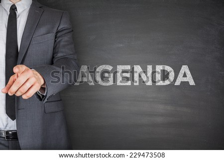 Agenda on blackboard with businessman hand holding chalk - stock photo