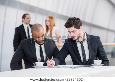 Agenda. Two successful businessman sitting at a desk holding papers in his hands and looking at documents while their colleagues standing in the background and talking to each other - stock photo