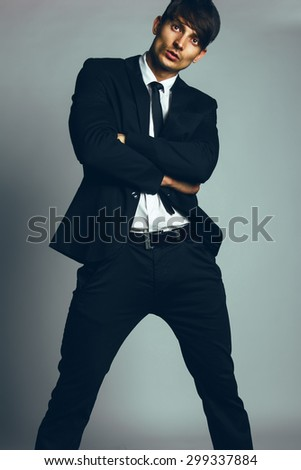 Agent 007 concept. Handsome young man with short hair wearing classic black&white suit and tie posing over gray background. Classic style. Studio shot - stock photo