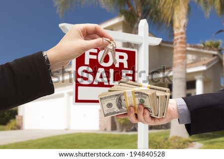 Agent Handing Over Keys as Buyer is Handing Over Cash for House with Home and For Sale Real Estate Sign Behind. - stock photo