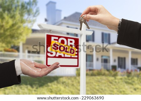 Agent Handing Over Keys to a New Home with Sold Real Estate Sign and House in the Background. - stock photo