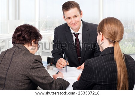 Agent or notary public signing documents with customers
