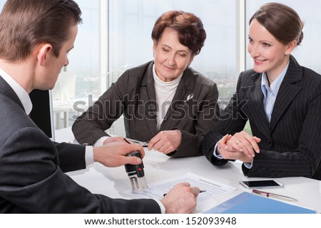 Agent (or notary public) signing documents with senior woman and her daughter - stock photo