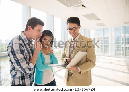Agent showing project of the house on the laptop to the young couple - stock photo