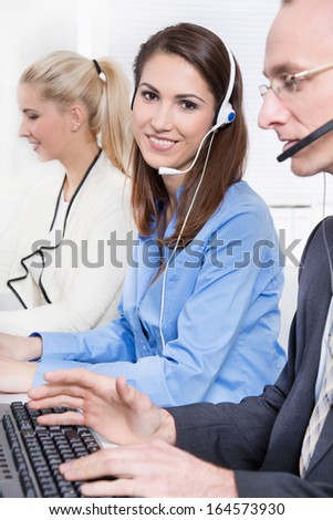 Agent smiling while working in a call-center - with head-set. - stock photo