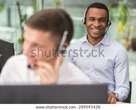 Agent smiling while working on his computer with colleague next to him. - stock photo