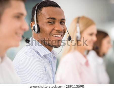 Agent smiling while working on his computer with colleagues next to him. - stock photo