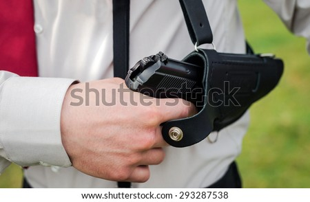Agent wearing white shirt drawing gun from holster - stock photo