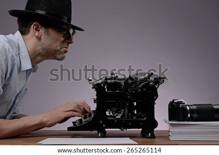 Agent with an old type writer and a vintage camera in a dark office - stock photo