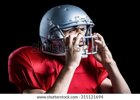 Aggressive American football player holding helmet while playing against black background
