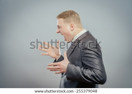 Aggressive businessman. Side view of angry young businessman shouting and gesturing  - stock photo