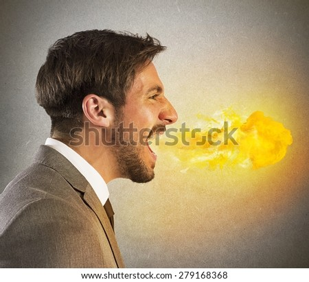 Aggressive businessman spits fire from his mouth - stock photo