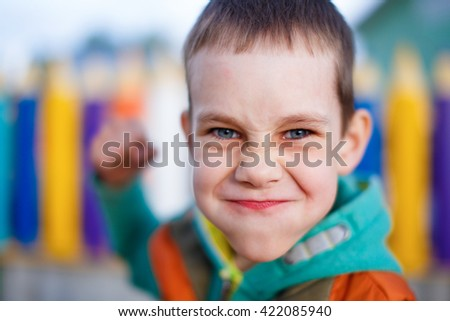 aggressive child raised his fist to strike. boy contorted with anger face fighting. selective focus - stock photo
