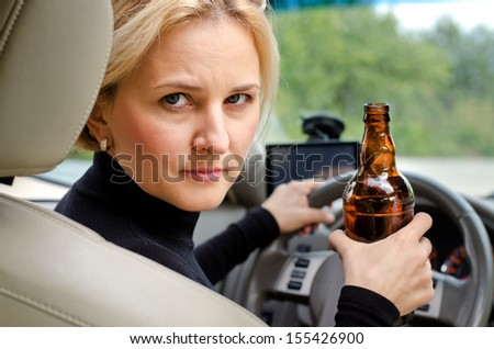 Aggressive drunk woman driver holding a bottle of alcohol turning round in the drivers seat to glare into the back passenger compartment at the viewer - stock photo