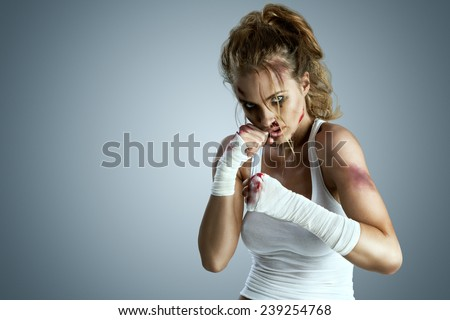 Aggressive female fighter with bruises wearing bloody bandage on her fists, standing in boxing defense position, ready to fight on a neutral grey studio background. - stock photo