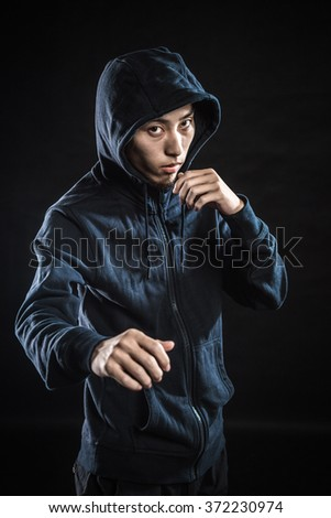 Aggressive fighter in hood while punching against black background - stock photo