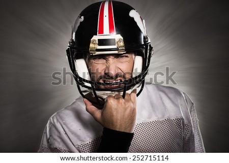Aggressive football player with protective helmet posing - stock photo