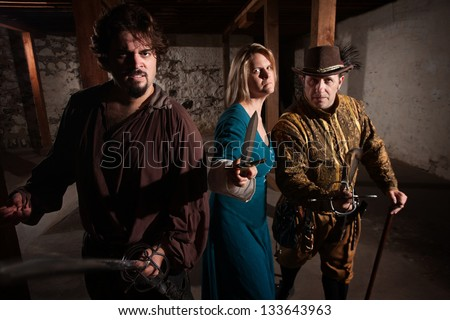 Aggressive group of people in medieval clothing with weapons