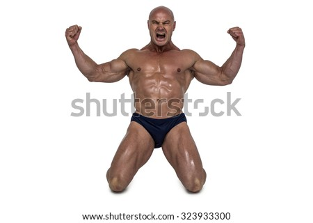 Aggressive man kneeling down with arms outstretched against white background - stock photo