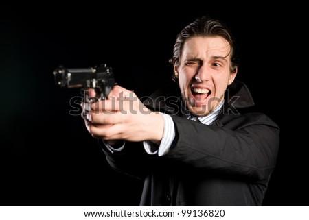 Aggressive man shooting a gun - stock photo