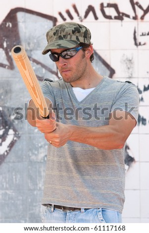 aggressive man with a stick in a hand - stock photo