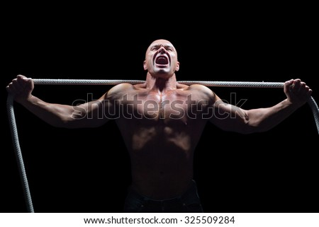 Aggressive man with arms outstretched holding rope against black background - stock photo