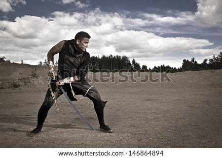 aggressive man with sword - stock photo