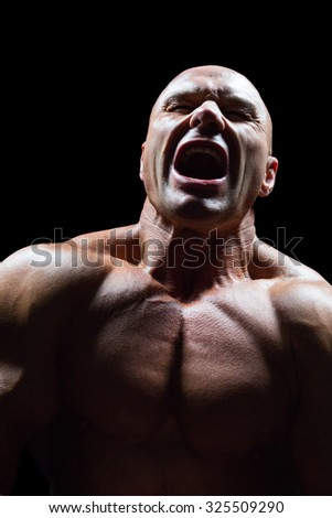 Aggressive muscular man against black background - stock photo