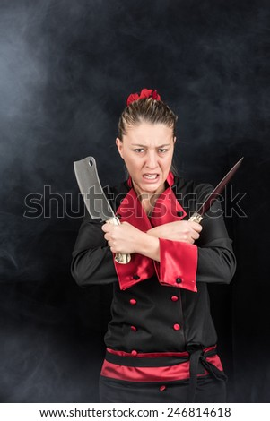 Aggressive psycho woman chef with mean expression holding knives - stock photo