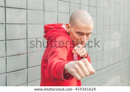 Aggressive street fighter in a red hoodie shows his fists