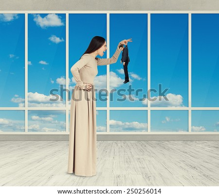 aggressive woman holding small man and yelling. photo in room with big windows - stock photo
