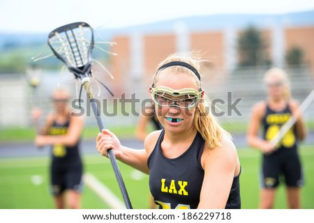 Aggressive women's lacrosse player with teammates in background. She is wearing full protective gear and holding her lacrosse stick. - stock photo